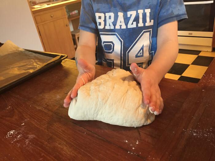 Christian på 8 år er i gang med at ælte dejen til hotdogsbrødene