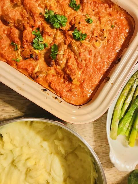 Ovnbagt ret med kotelet og pølser i tomat-flødesauce